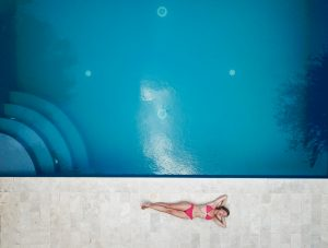 woman-lying-on-floor-near-pool-1460742